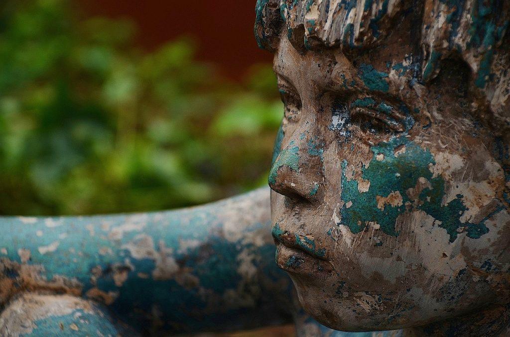 Die Statue von einem Kind, einem Jungen, die mit abgeblätterter grüner Farbe bedeckt ist