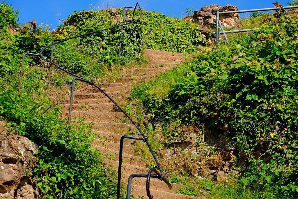 Kantige und rauhe Wahrheit: eine steile und verwinkelte Treppe führt an Natursteinen und Gestrüpp entlang