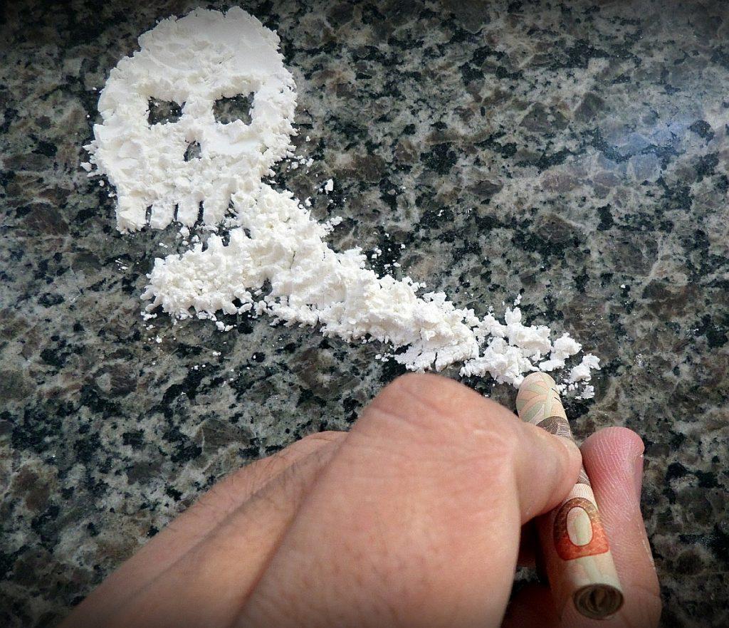 Land des Vergessens: Kokain liegt in Form eines Totenkopfes auf dem Tisch, eine Hand mit zusammengerolltem 50-Euro-Schein hält sich bereit, um es zu schnupfen.