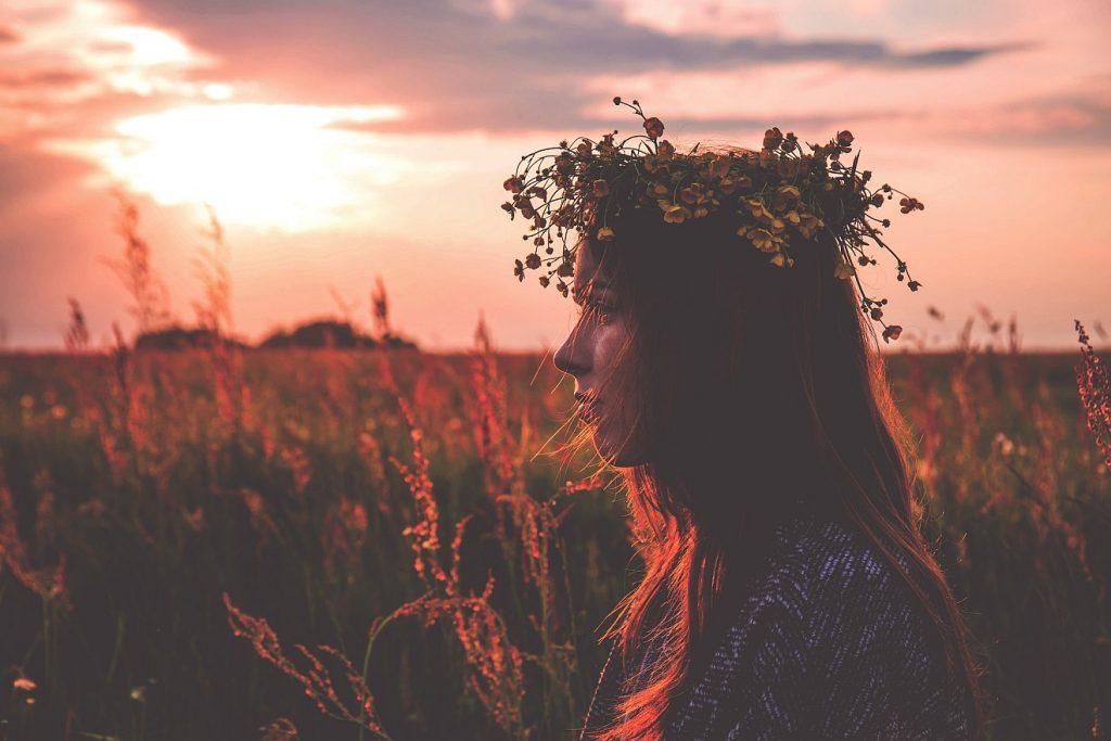 Ehre und Herrlichkeit: Eine Frau vor einer Blumenwiese bei Sonnenuntergang mit einer Krone aus Blumen