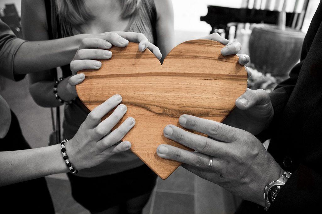 Liebe über den Tod hinaus: Hände einer Trauergesellschaft (in Schwarzweiß) halten ein Herz aus Holz (farbig)