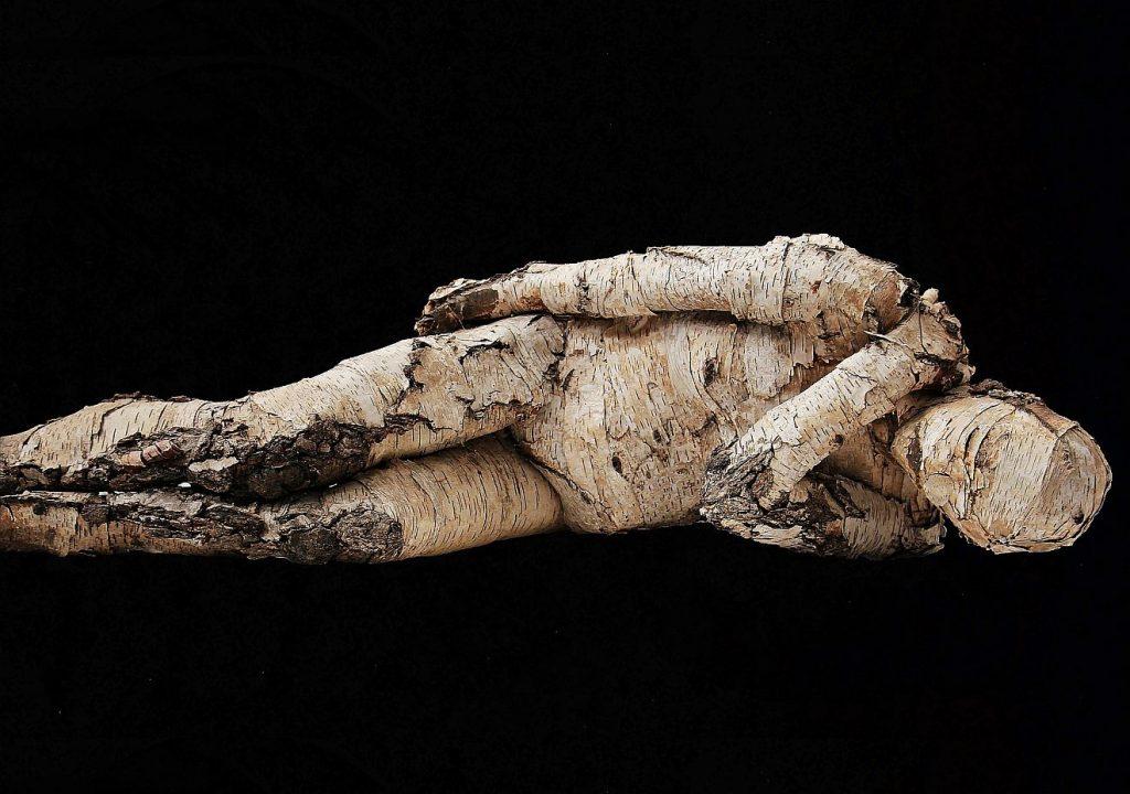 Fürglaube: Eine menschliche Gestalt aus Birkenrinde liegt in sich verschlossen vor einem schwarzen Hintergrund.