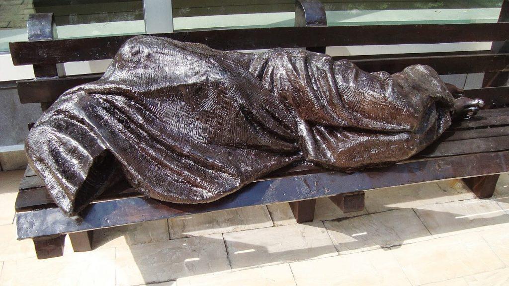In der Kälte des Winters erfroren: Statue eines Obdachlosen, der auf einer Parkbank schläft