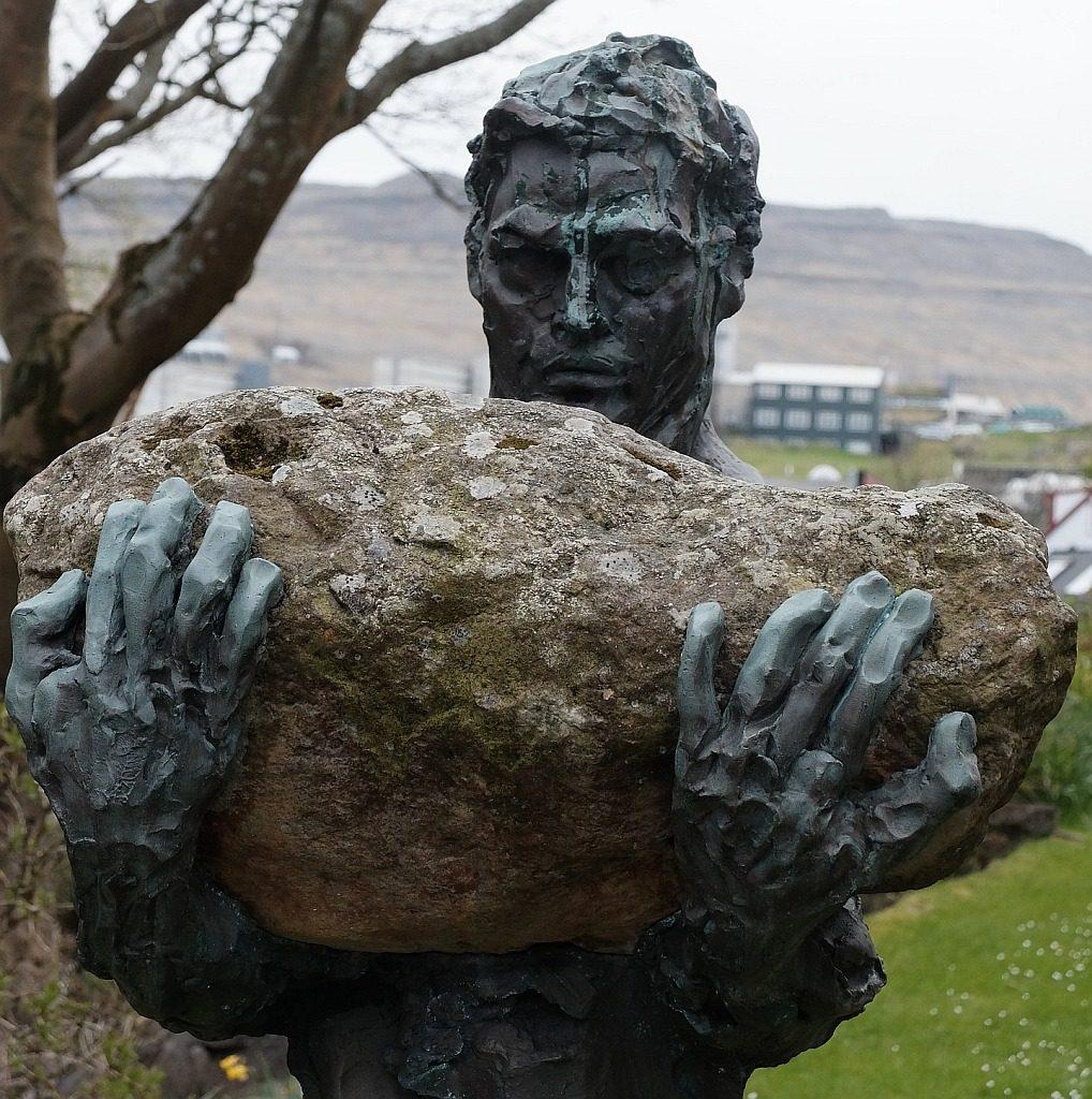 Es war mir zu schwer: Skulptur eines Mannes, der einen schweren Stein vor sich auf den Armen trägt.