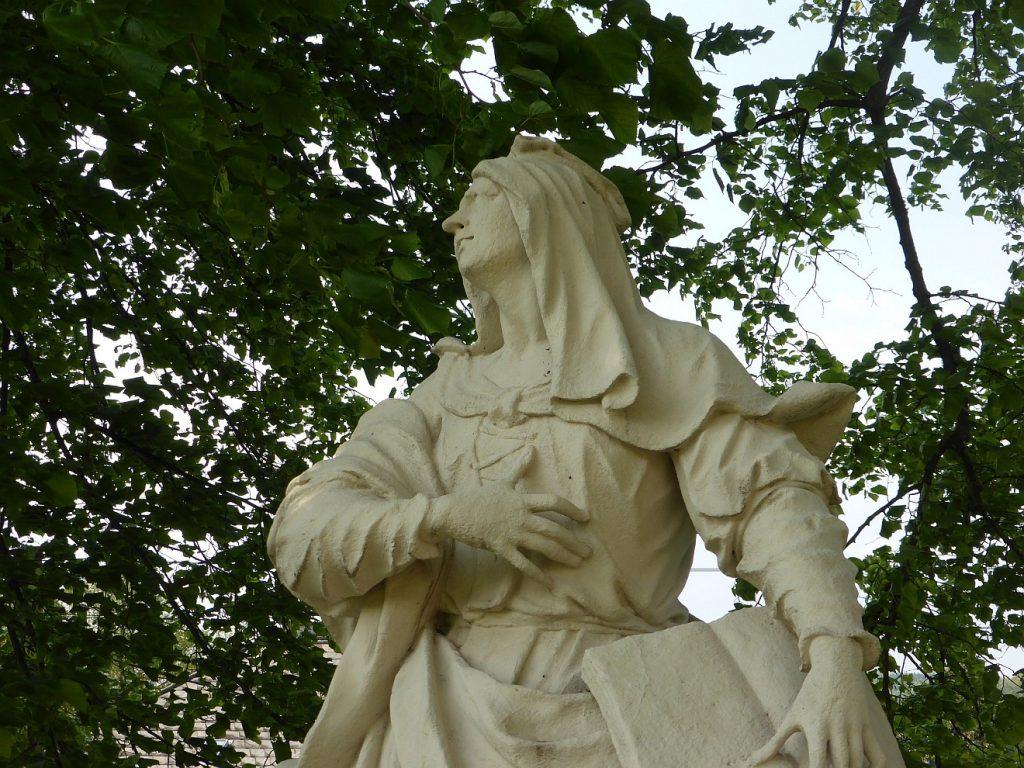 Die Skulptur einer Kämpferin mit der linken Hand auf einem Buch, der rechten auf ihrer Brust