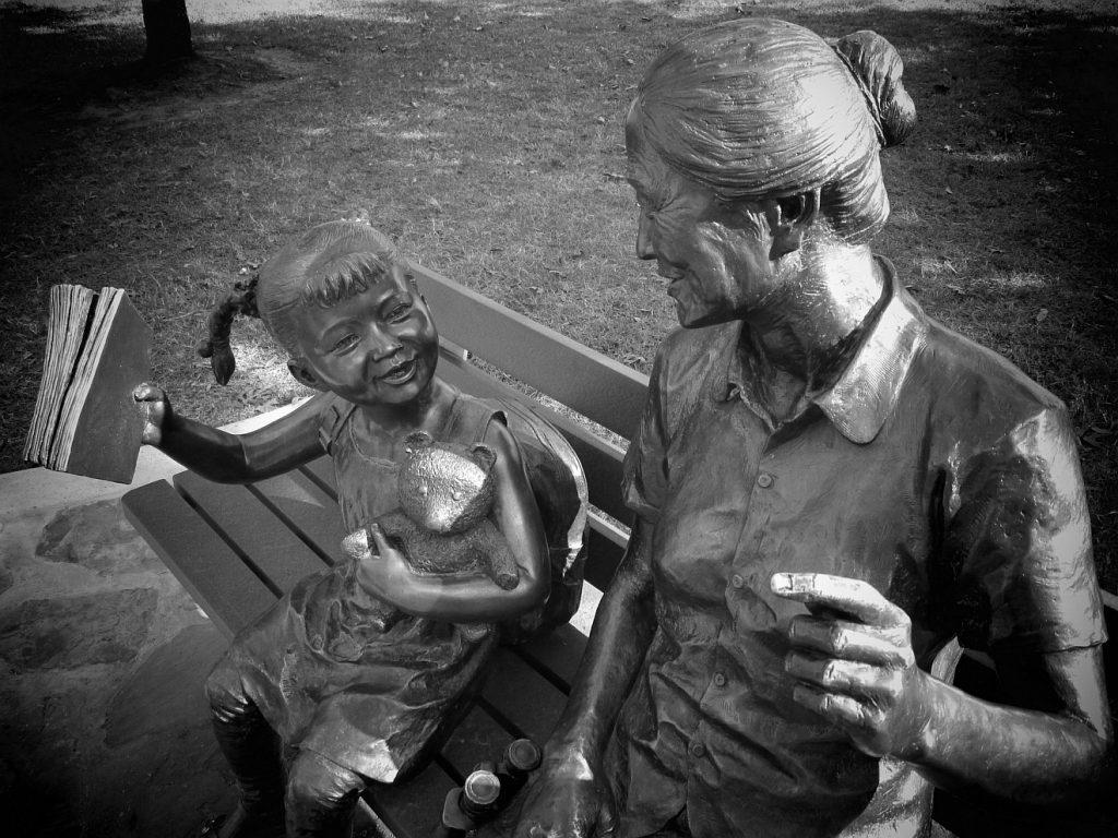 Skulpturen von Enkelkind und Oma, die auf einer Bank sitzen.