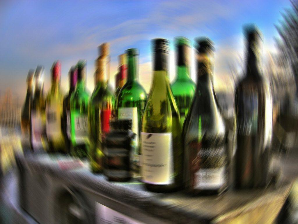 Im Kampf gegen die Sucht: Flaschen voller Alkohol, unscharf aufgenommen, als ob sich alles dreht