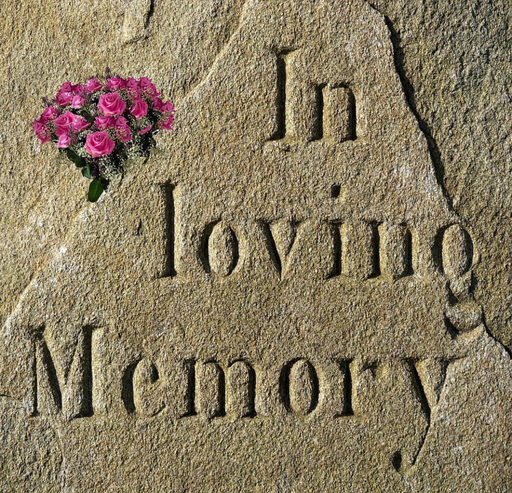 """Wie trauern Kinder und Kindeskinder? Ein Grabstein mit einem Blumenstrauß und der Inschrift: """"In loving Memory"""" = """"In liebender Erinnerung"""""""
