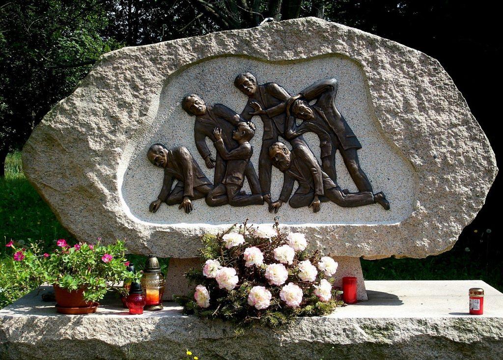 Verlorene Heimat: Auf einem Grabstein sind Menschen dargestellt, die zu Boden gedrückt und vertrieben werden