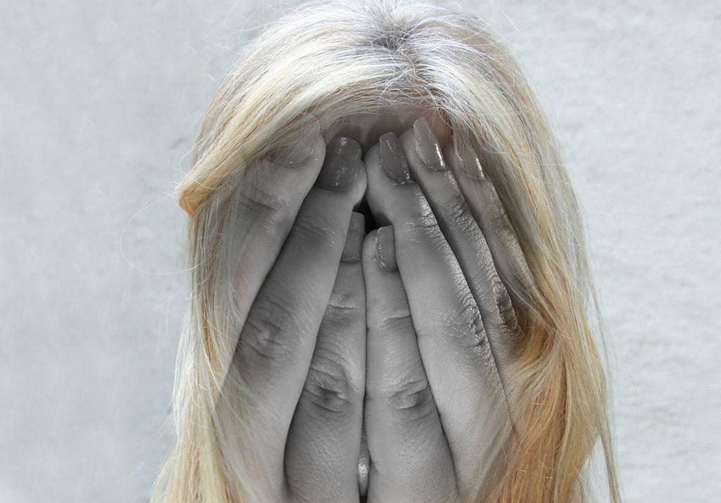 Sich das Leben nehmen: Eine Frau, die sich verzweifelt beide Hände vor das Gesicht hält