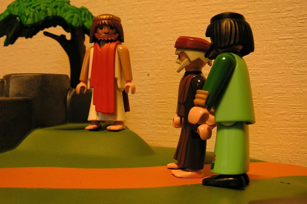 Zum Thema Kirchenaustritte: Jesus als Playmobil-Figur steht zwei Jüngern gegenüber