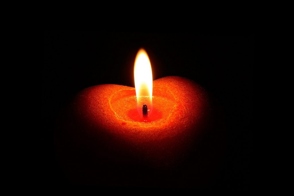 Eine rote Kerze als Lichtbringer im Dunkeln, von der man nur die Flamme inmitten eines herzförmigen roten Wachsrandes sieht.