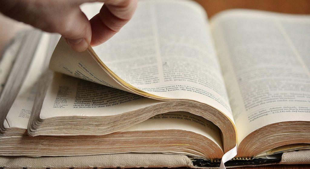Die Bibel als Tagebuch der Menschheit: Jemand blättert vorsichtig durch die Bibel.
