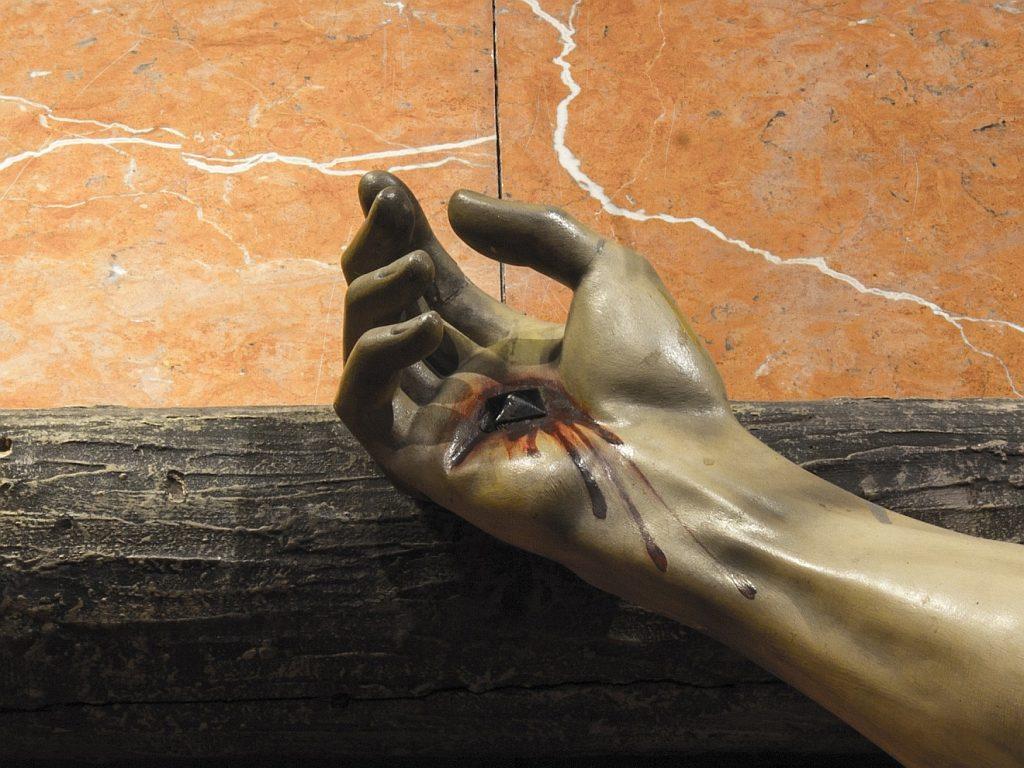 Jesu ans Kreuz genagelte Hand, aus der Blut austritt, anscheinend aus einer Wunde in Form eines Dreiecks.