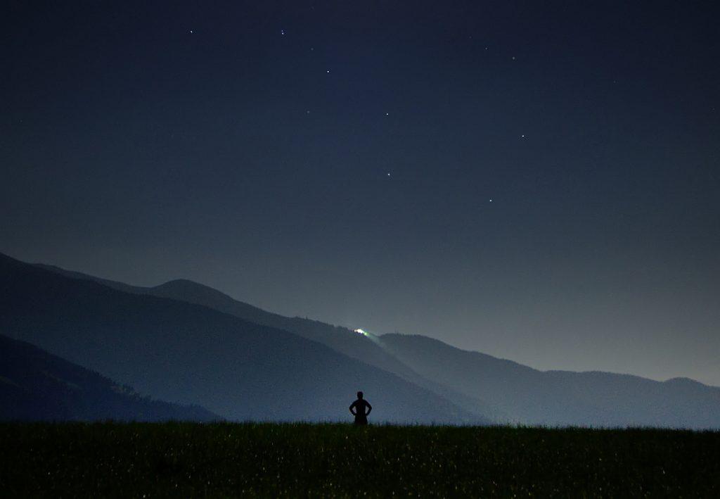 Nachtlichter sind zu sehen für einen einsamen Menschen auf einer Wiese - das Sternbild des Wagens und hinter einer Bergkuppe das Licht eines Gebäudes