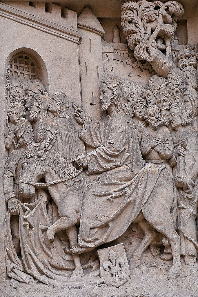 Steinrelief: Jesus zieht am Anfang der Karwoche auf einem Esel in Jerusalem ein