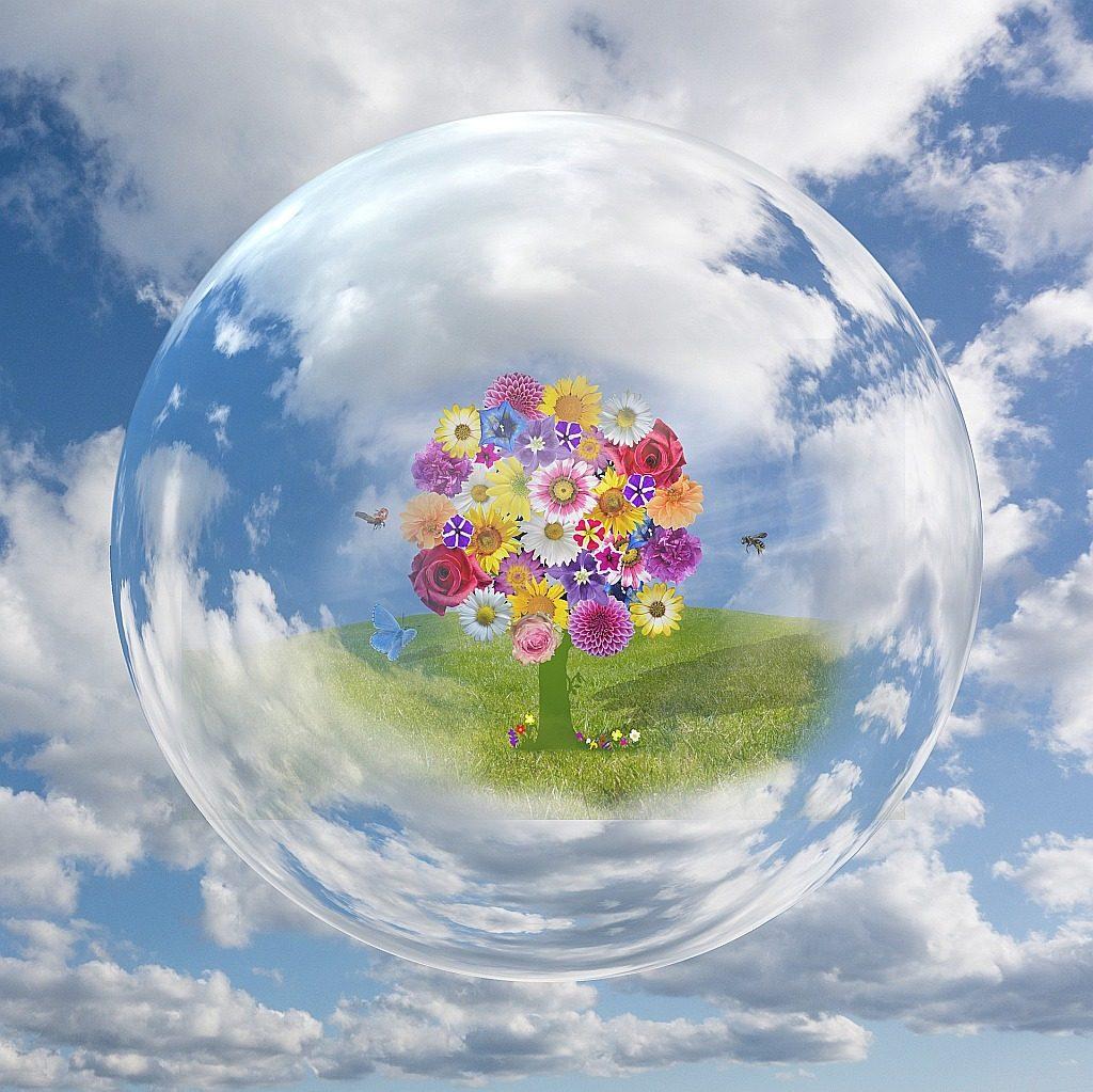 Ein Baum mit Blumenblüten auf einer Wiese in einer durchsichtigen Kugel vor einem blauen Himmel mit weißen Wolken - Symbol für die Schöpferkraft Gottes, die Lebensräume schafft und bevölkert