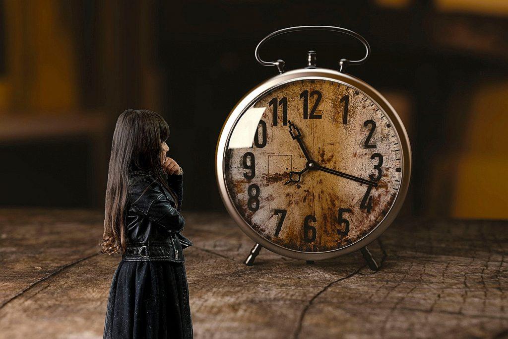 Ein Mädchen steht einem übermäßig großen schmutzigen Wecker gegenüber - kann es warten?