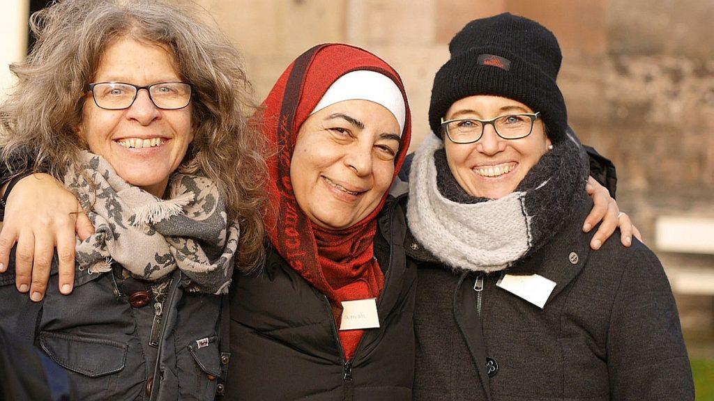 Eine Frau mit Kopftuch zwischen zwei Frauen mit und ohne Hut - Symbolfoto für Integration