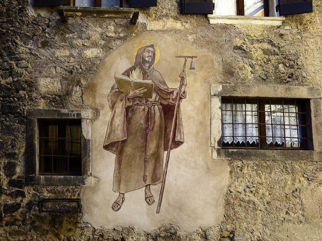 Ein Wandbild auf einer schmutzigen Wohnhausfassade: Ein Mönch hält eine Bibel in der Hand, aus der Flammen schlagen