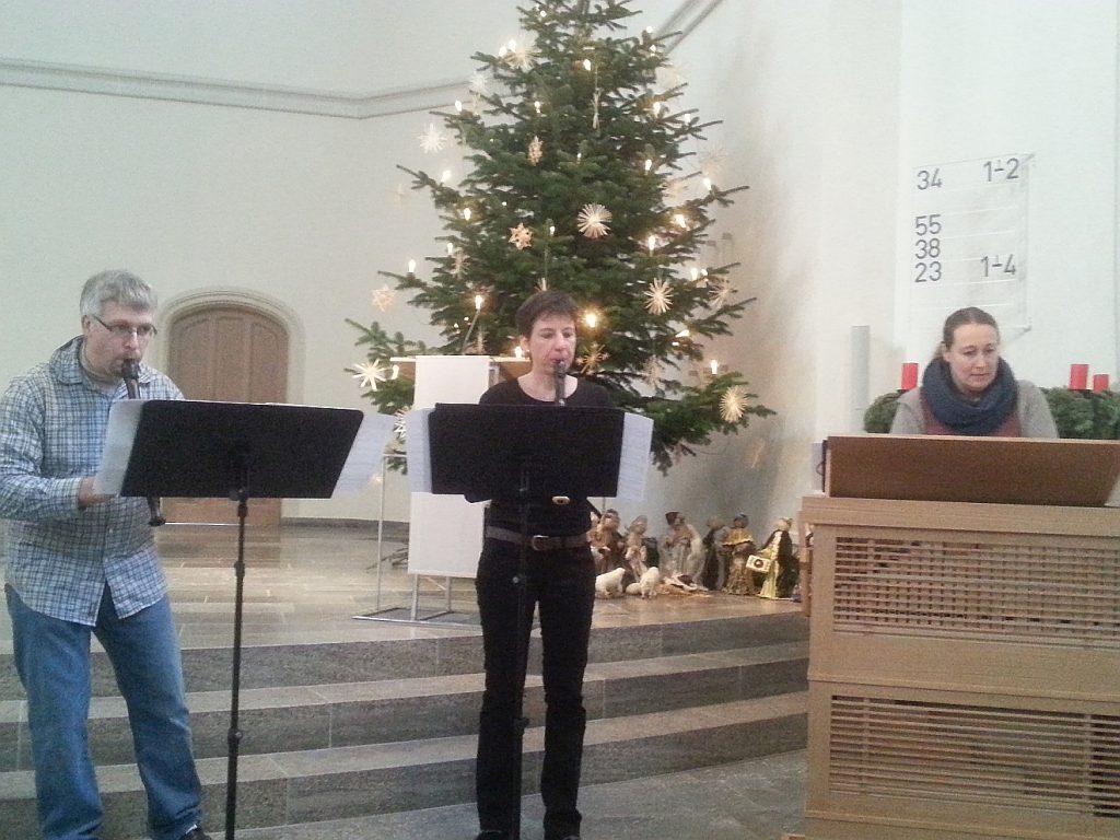 Ein Mann und eine Frau spielen Flöte, eine Frau spielt eine Kasten-Orgel.