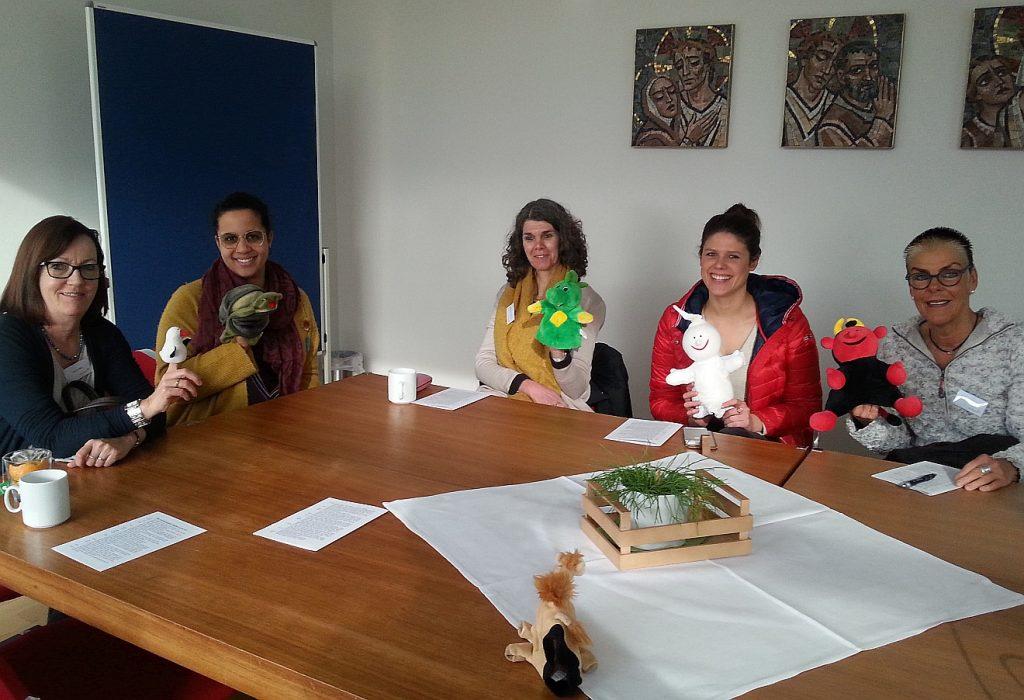 Fünf Frauen am Tisch mit den Handpuppen Fischli, Zappi, Nappi, Gabi und Lutz in der Hand - außerdem sitzt Jamal auf dem Tisch.