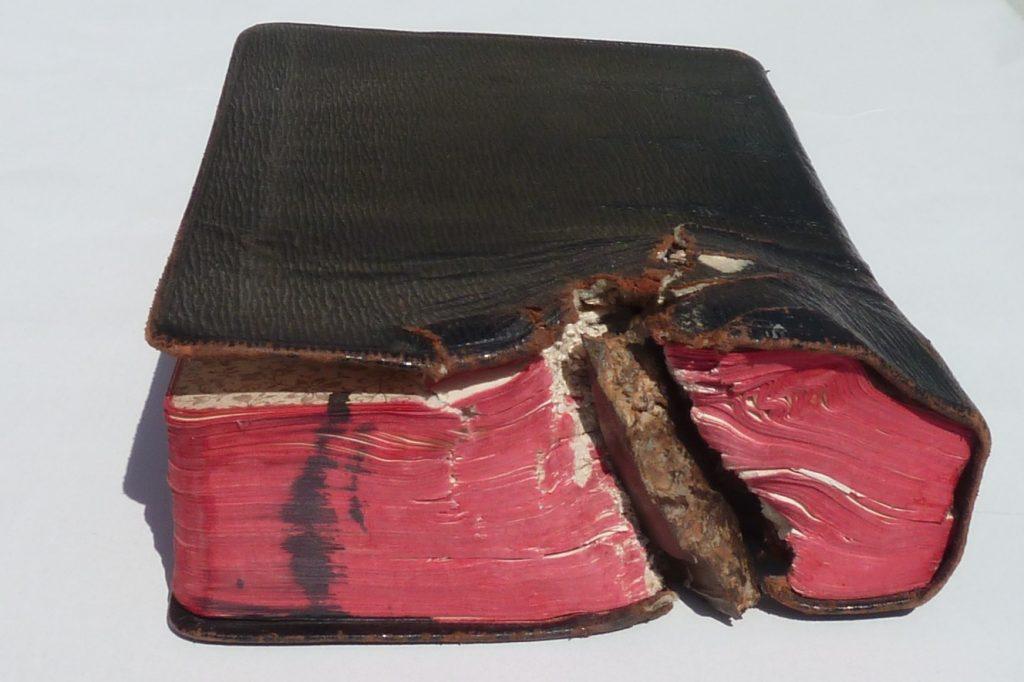 Das Bild einer Bibel, in der ein Granatsplitter steckt - Bild für ein Buch, das auch viele grausame Geschichten enthält.