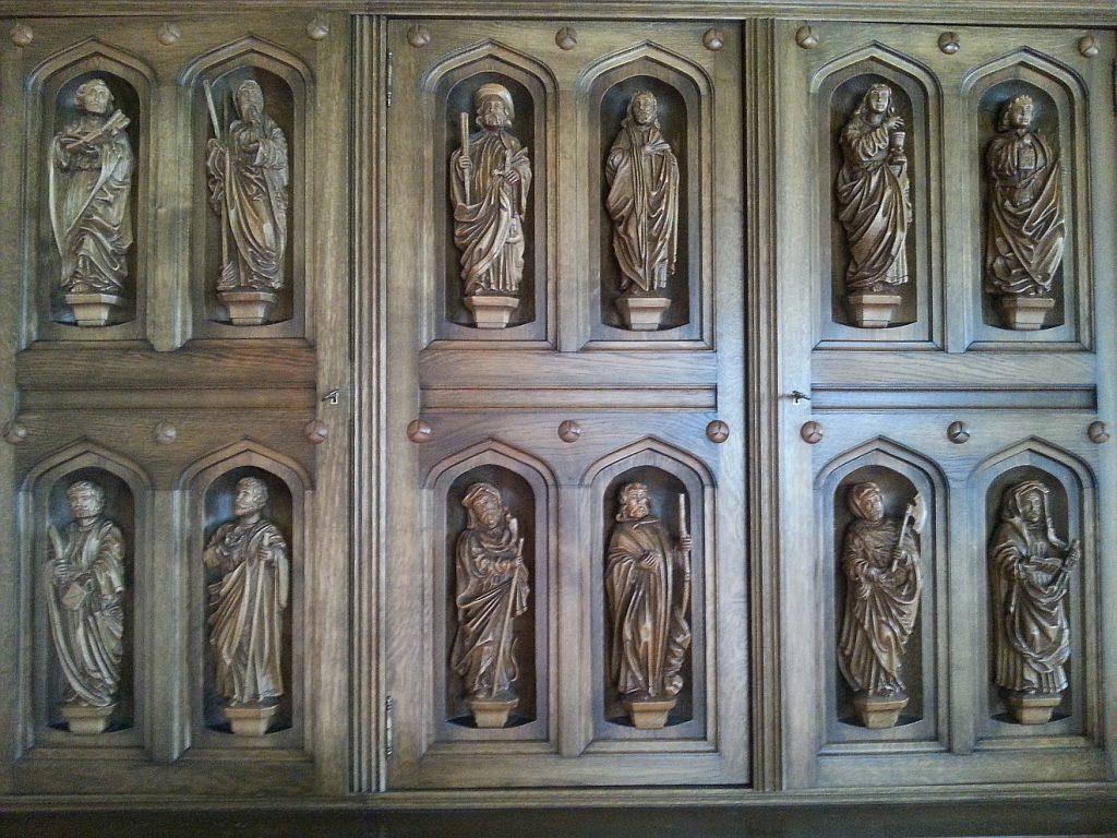 Schnitzereien der 12 Apostel an den Türen eines Wohnzimmerschranks