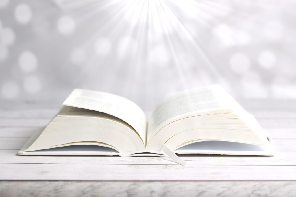Eine aufgeschlagene Bibel, angestrahlt von einer Lichtquelle, die von oben kommt, wie vom Himmel - muss man sie als wortwörtlich offenbartes Wort Gottes lesen?