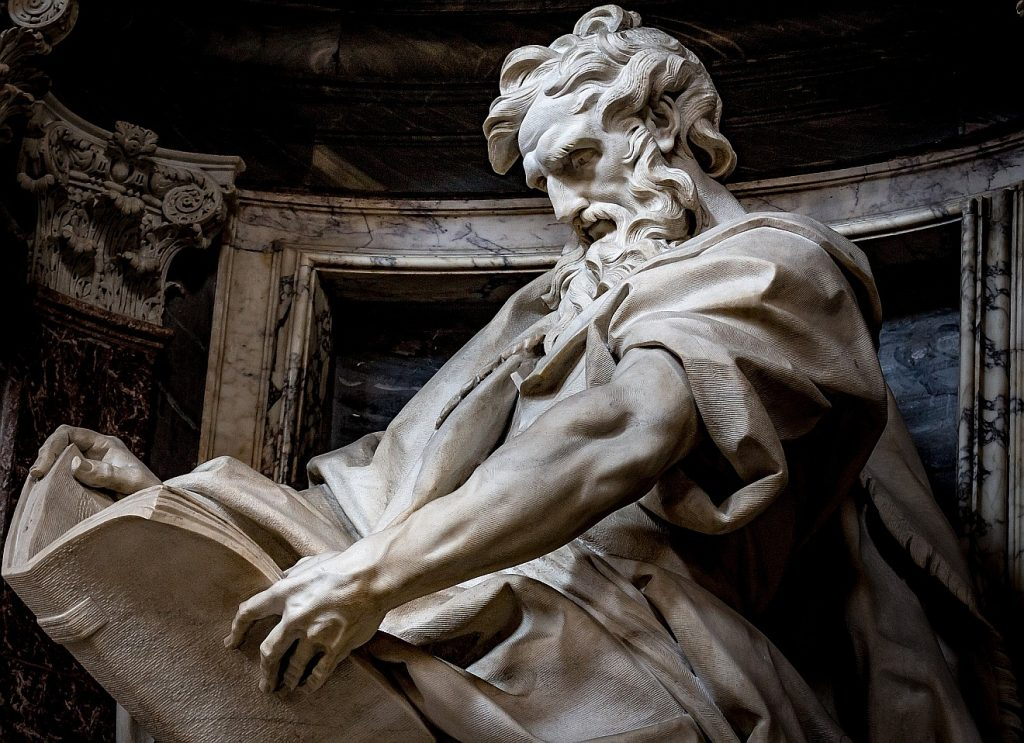 Statue des sitzenden Evangelisten Matthäus, der mit prüfenden Blick in sein Evangelium schaut: Er war ein Mensch, auch er konnte irren.