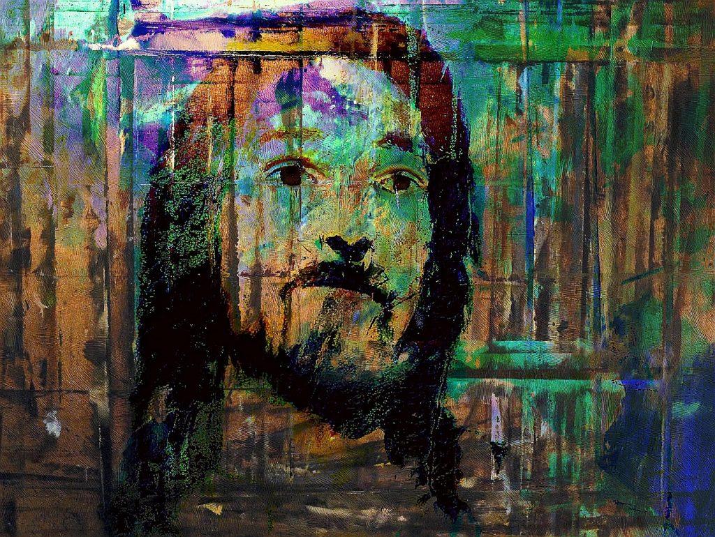 Eine abstrakt wirkende Darstellung des Gesichtes Jesu, mit grüner und blauer Farbe im Hintergrund, auf eine Bretterwand aufgetragen, aber nicht deckend