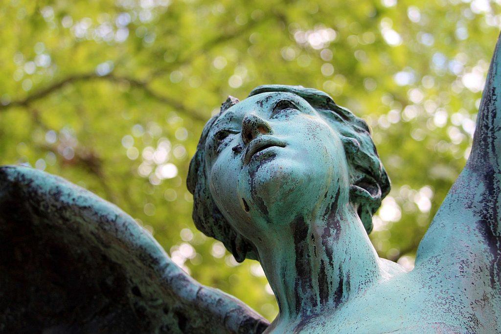 Das Gesicht einer Engelskulptur, von unten fotografiert, nach oben oder vorn blickend
