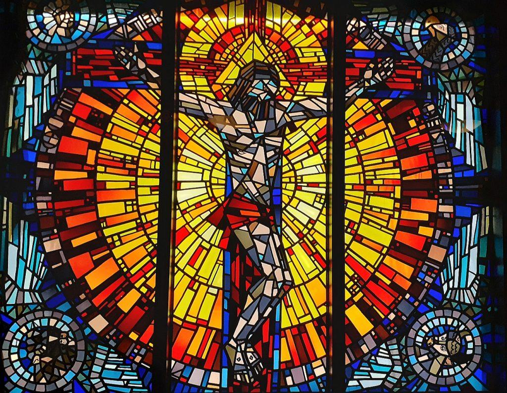 Jesus am Kreuz, umleuchtet von einer rot und gelb strahlenden Sonne, auf einem Fensterbild in der Kapelle des Evangelischen Krankenhauses Gießen