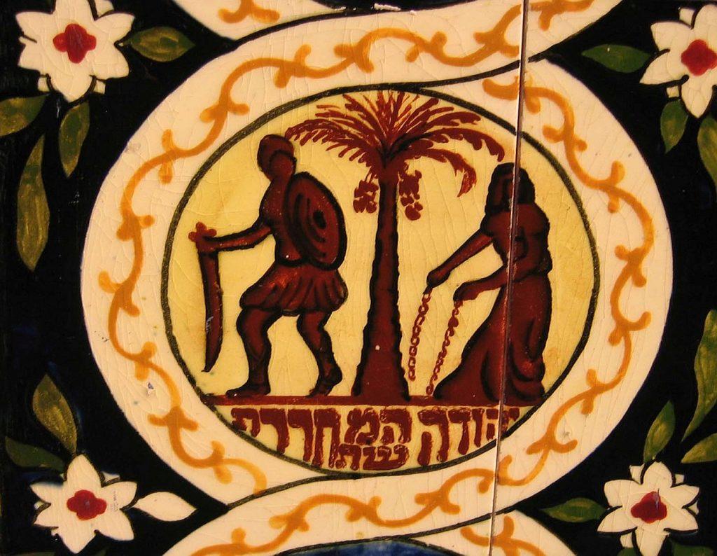 Darstellung einer Palme, neben der links ein Römer mit Schwert und Schild steht, während rechts eine jüdische Frau zertrennte Ketten in der Hand hält. darunter steht die hebräische Inschrift: Yehuda hamishtachreret.