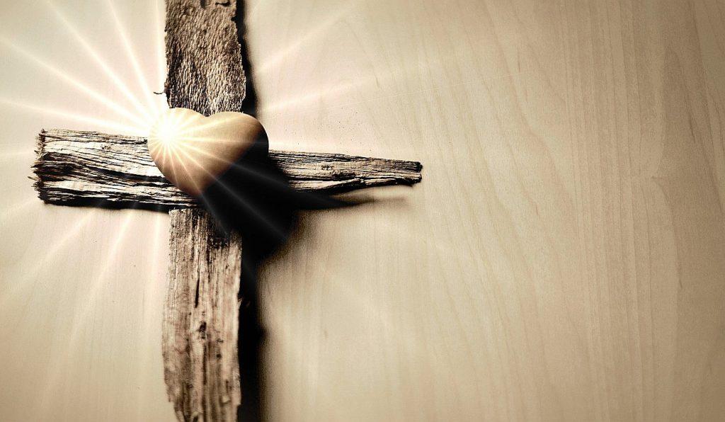 Ein Kreuz aus zwei Holzstücken, auf denen ein Herz aus Stein liegt, von dem Strahlen ausgehen.