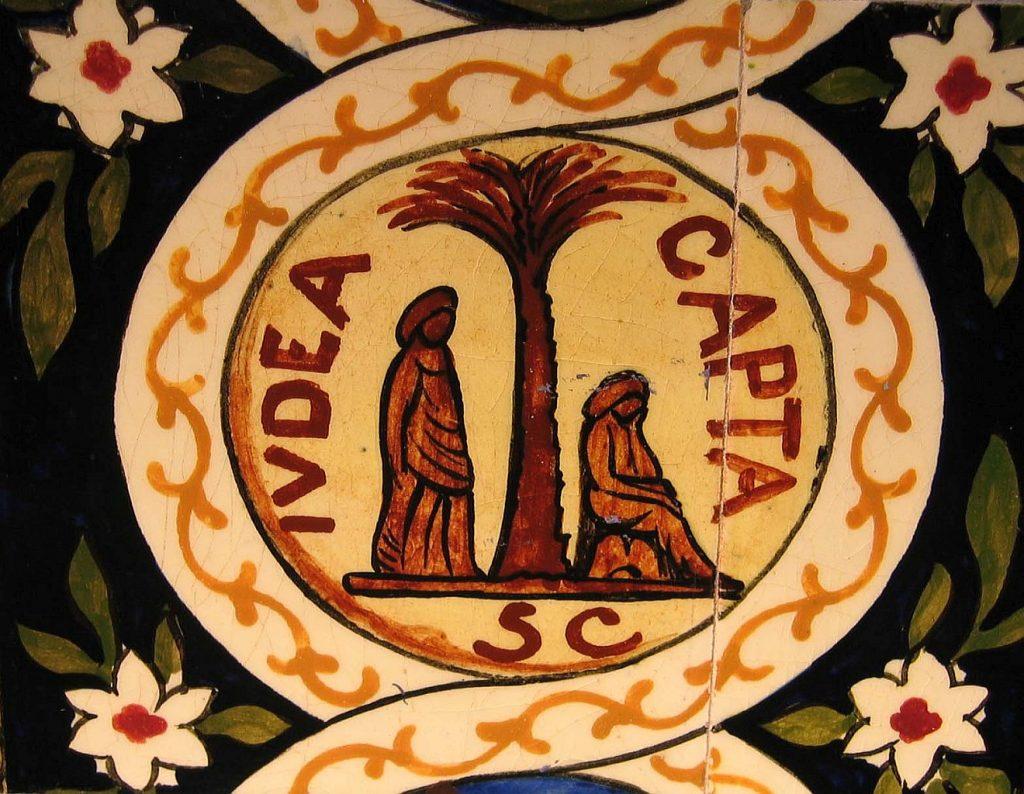 """Zeichnung einer Palme mit einem Römer auf ihrer linken und einer trauernden jüdischen Frau, die auf der rechten Seite sitzt. Das Bild symbolisiert die Unterdrückung nach der Judäischen Krieg 70 n. Chr. mit den Worten """"Judaea capta""""."""